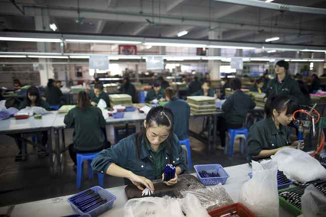 Workers assemble pens at the factory in Guangzhou, Guangdong province. China's economy is slowing, spurring policy makers to loosen monetary policy and pledge targeted steps to counter downward pressure.