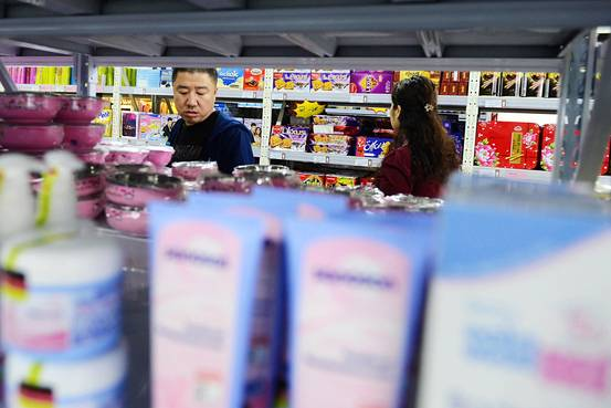 Customers choose goods from a supermarket that sells imported products.